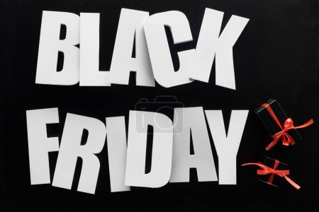 top view of black Friday lettering and presents isolated on black