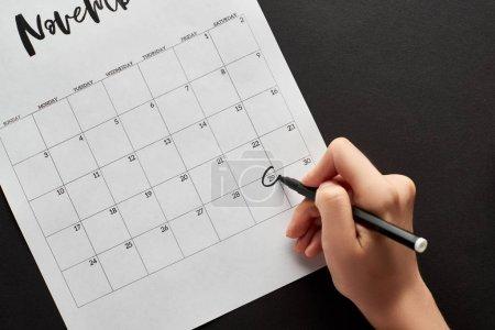 Photo pour Vue recadrée de la femme marquant la date du vendredi noir dans le calendrier sur fond noir - image libre de droit