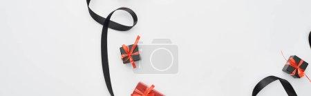 Photo pour Vue du dessus du ruban noir et des boîtes-cadeaux rouges sur fond blanc, vue panoramique - image libre de droit