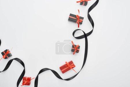 Photo pour Vue du dessus du ruban noir et des boîtes-cadeaux rouges sur fond blanc - image libre de droit