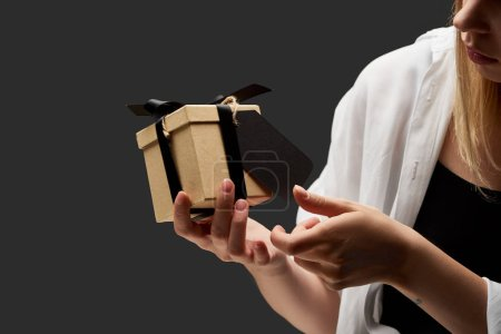cropped view of woman holding gift box with black blank label in hand isolated on black