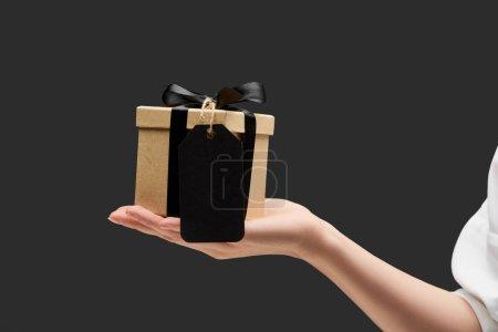 Photo pour Vue recadrée de la femme tenant boîte cadeau avec étiquette vierge noire à la main isolé sur noir - image libre de droit