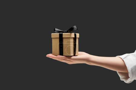 Photo for Cropped view of woman holding gift box in hand isolated on black - Royalty Free Image