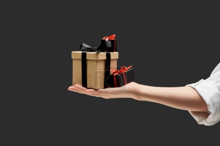 cropped view of woman holding gift boxes in hand isolated on black