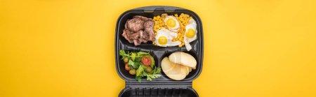 Photo pour Plan panoramique de l'emballage écologique avec du maïs, de la viande, des œufs frits, des pommes et de la salade isolés sur jaune - image libre de droit