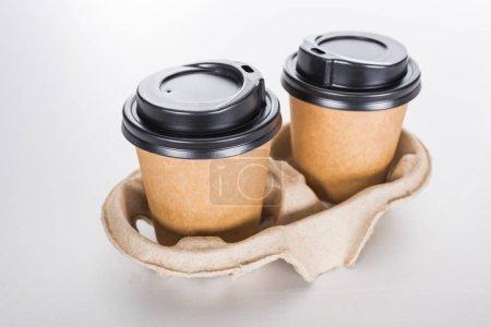Photo pour Tasses en papier avec café dans un plateau en carton sur fond blanc - image libre de droit