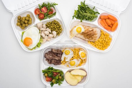 Photo pour Top view of eco packages with apples, vegetables, meat, fried eggs and salads on white background - image libre de droit