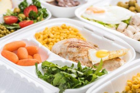Selektiver Fokus des Ökopakets mit Gemüse, Fleisch, Spiegelei und Rucola auf weißem Hintergrund