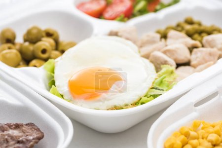 Photo for Selective focus of eco package with vegetables, meat, fried egg and salad on white background - Royalty Free Image
