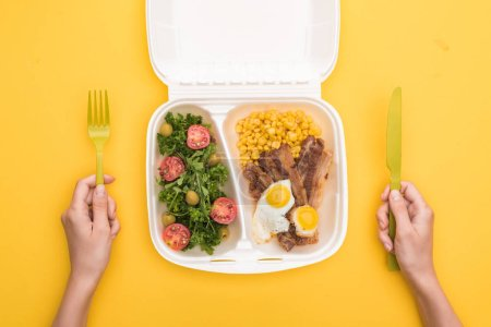 Photo for Cropped view of woman holding plastic fork, knife and eco package with corn, meat, fried eggs and salad isolated on yellow - Royalty Free Image