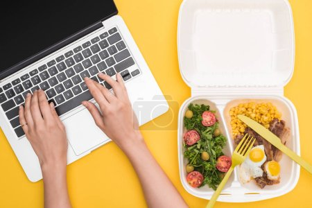 Photo for Cropped view of woman using laptop and eco package with corn, meat, fried eggs and salad isolated on yellow - Royalty Free Image