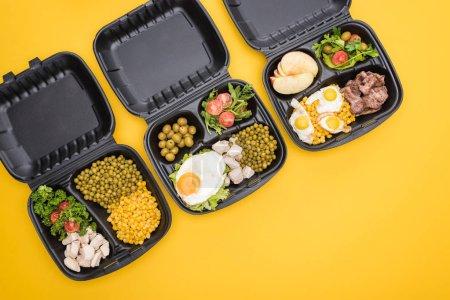 Photo pour Vue de dessus des emballages écologiques avec pommes, légumes, viande, œufs frits et salades isolés sur jaune - image libre de droit
