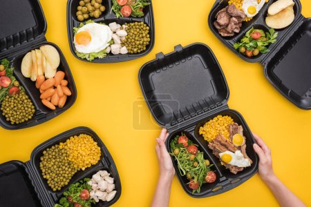 Photo for Cropped view of woman holding eco package with corn, meat, fried eggs and salad isolated on yellow - Royalty Free Image