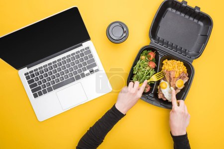 Photo for Cropped view of woman eating from eco package with corn, meat, fried eggs and salad isolated on yellow - Royalty Free Image