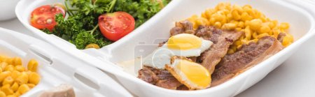 Photo for Panoramic shot of eco package with corn, meat, fried eggs and salad on white background - Royalty Free Image