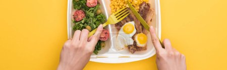 Photo for Panoramic shot of woman eating from eco package with corn, meat, fried eggs and salad isolated on yellow - Royalty Free Image