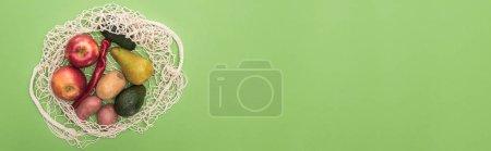 Foto de Vista superior de verduras y frutas en bolsa de cuerda aislada en verde - Imagen libre de derechos