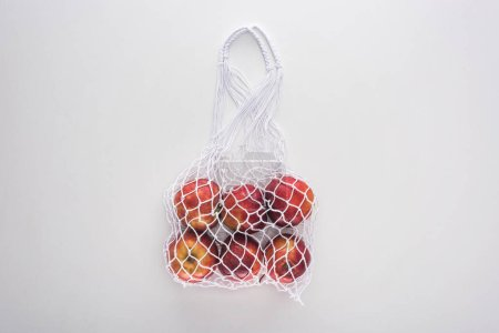Photo for Top view of apples in eco friendly string bag isolated on white - Royalty Free Image