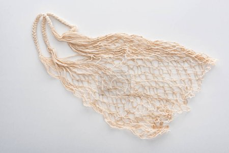 Photo for Top view of empty beige eco friendly string bag isolated on white - Royalty Free Image