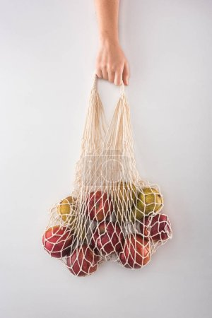 Photo for Cropped view of woman holding eco friendly string bag with apples and pears isolated on white - Royalty Free Image