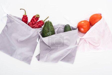 Foto de Vista superior de aguacates frescos, tomates y chiles en bolsas ecológicas aisladas en blanco - Imagen libre de derechos