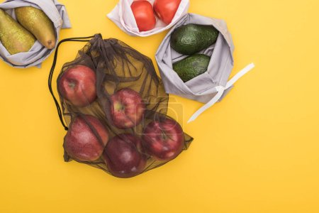 Photo for Top view of ripe apples, pears, tomatoes, avocado in eco friendly bags isolated on yellow - Royalty Free Image