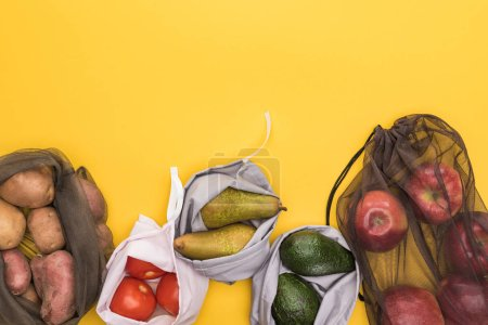 Photo for Top view of ripe apples, pears, tomatoes, avocado and potatoes in eco friendly bags isolated on yellow - Royalty Free Image