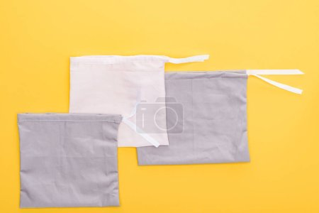 Photo pour Vue du dessus de sacs écologiques en coton blanc et gris isolés sur jaune - image libre de droit