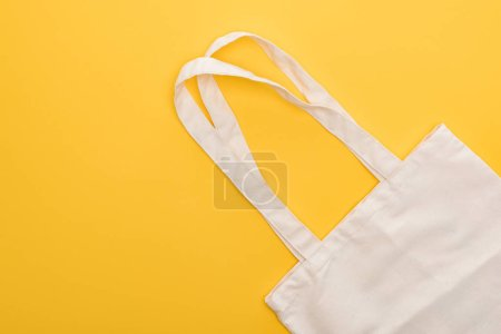 Photo for Top view of cotton white eco friendly bag isolated on yellow - Royalty Free Image