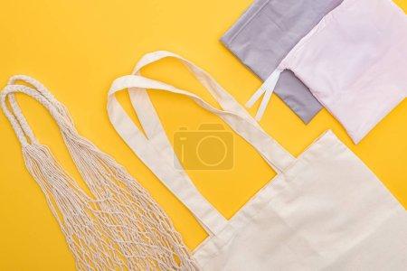 Photo pour Vue supérieure des sacs écologiques vides d'isolement sur le jaune - image libre de droit
