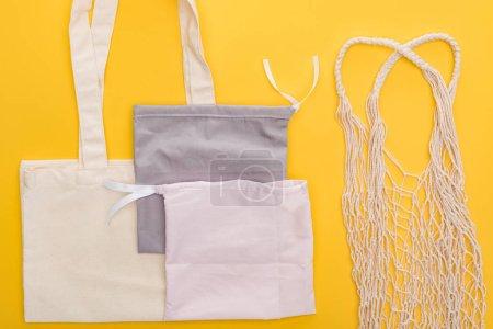 Foto de Vista superior de bolsas ecológicas vacías aisladas en amarillo - Imagen libre de derechos