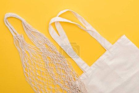 Photo pour Vue du dessus des sacs en coton blanc et des sacs à ficelle isolés sur jaune - image libre de droit
