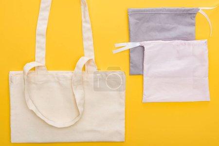 Photo pour Vue du haut des sacs écologiques de coton d'isolement sur le jaune - image libre de droit