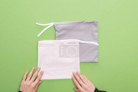 Foto de Manos de mujer vista recortada sin uso y bolsas ecológicas aisladas en verde - Imagen libre de derechos
