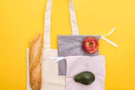 Foto de Vista superior de manzana, baguette y aguacate en bolsas ecológicas aisladas en amarillo - Imagen libre de derechos