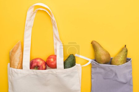 Photo for Top view of ripe fruits, vegetables and baguette in eco friendly bags isolated on yellow - Royalty Free Image