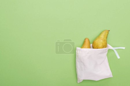 Photo for Top view of pears in eco friendly white bag isolated on green - Royalty Free Image