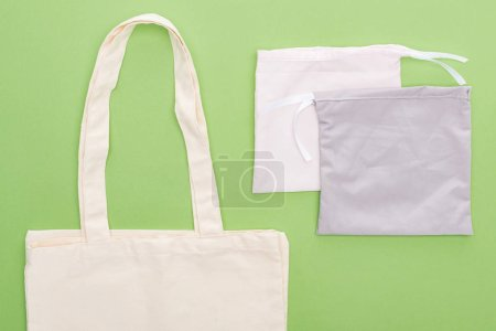 Photo for Top view of empty cotton eco bags isolated on green - Royalty Free Image