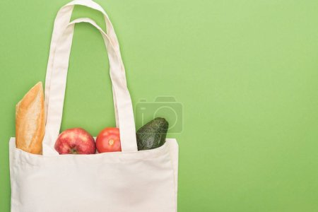 Photo for Top view of tomato, avocado, apple and baguette in eco friendly bag isolated on green - Royalty Free Image