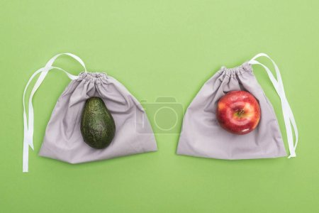 Photo for Top view of avocado and apple on eco friendly bags isolated on green - Royalty Free Image