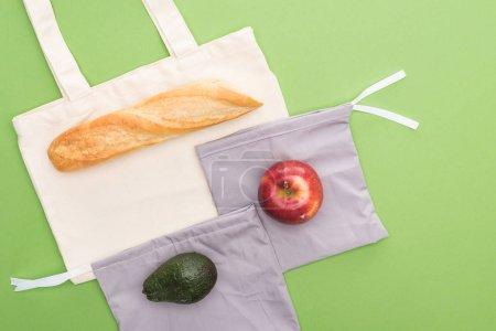 Foto de Vista superior de baguette, manzana y aguacate en bolsas ecológicas aisladas en verde - Imagen libre de derechos