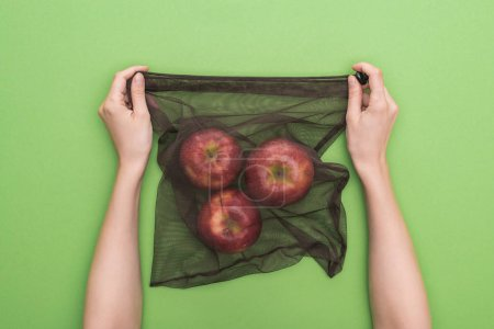 Photo for Partial view of woman holding red ripe apples in eco friendly bag isolated on green - Royalty Free Image
