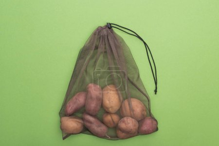 Photo for Top view of fresh whole potatoes in eco friendly bag isolated on green - Royalty Free Image