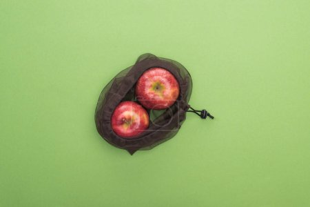 Photo for Top view of red ripe apples in eco friendly bag isolated on green - Royalty Free Image