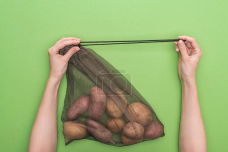 Photo for Cropped view of woman holding eco friendly bag with potatoes isolated on green - Royalty Free Image