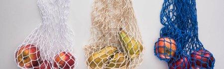 Photo pour Vue du haut des fruits dans les sacs de corde écologiques d'isolement sur le blanc, projectile panoramique - image libre de droit