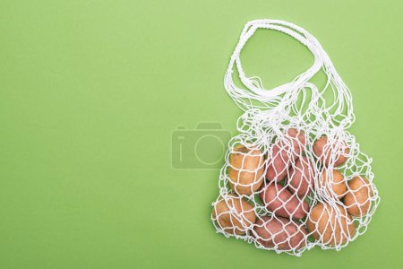 Photo for Top view of fresh potatoes in eco friendly string bag isolated on green - Royalty Free Image