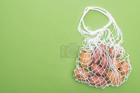 Foto de Vista superior de las patatas frescas en bolsa de cuerda ecológica aislada en verde - Imagen libre de derechos