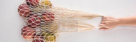 Photo pour Vue recadrée d'une femme tenant un sac à ficelle écologique avec des pommes et des poires isolées sur fond blanc, panoramique - image libre de droit