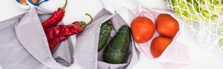 Photo for Top view of fresh avocados, tomatoes and chili peppers in eco friendly bags isolated on white, panoramic shot - Royalty Free Image